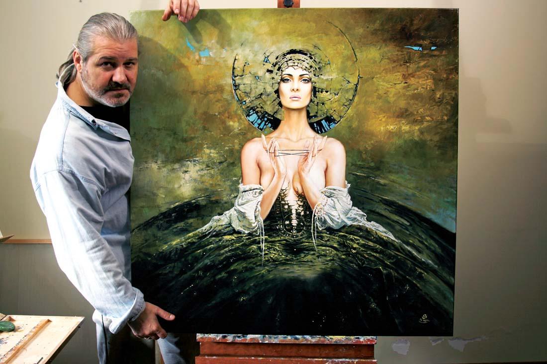 """Karol Bąk prezentuje obraz, który został namalowany specjalnie dla kwartalnika """"Artysta i Sztuka"""", aby pokazać proces jego powstawania."""
